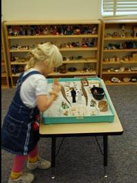 Дівчинка будує композицію в пісочниці. На задньому плані стелажі з іграшками для пісочної терапії.